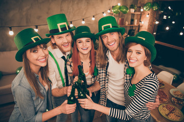Close up photo company buddies hands raise beer bottles laugh laughter in bar pub celebrating funny funky carefree every year tradition st paddy day holiday weekend vacation free time leisure rejoice