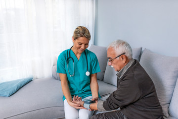 Heart work. Attentive caregiver using tonometer while elder man having breath problem