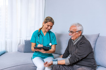 Nurse doing blood pressure monitoring for senior man at home. Close up photo of blood pressure measurement. Nurse measuring blood pressure of senior man at home. Smiling to each other.