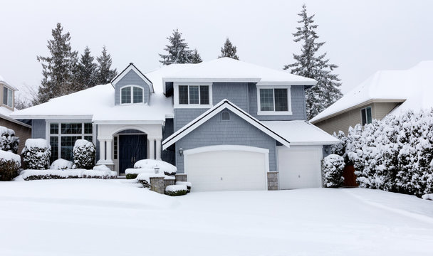 Snowing with residential Pacific Northwest home in background