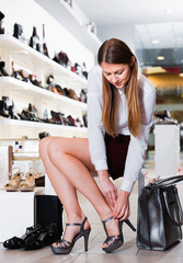 Young female is choosing summer shoes in shoes shop.