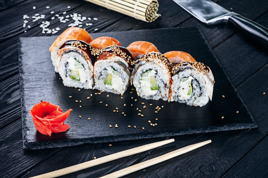 Served sushi rolls on black stone with chopsticks. Close up view on sushi on dark background. Traditional japanese cuisine. Restaurant, food menu, recipe, cafe concept. Lifestyle with copy space