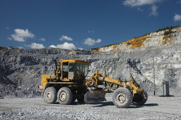 Grader in a quarry for limestone mining. Mining industry.