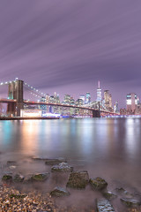 View on Financial district and Brooklyn bridge at night from East river beach with long exposure