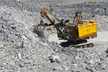 Excavator filled the ladle with rock ore before loading into the truck in the limestone quarry.
