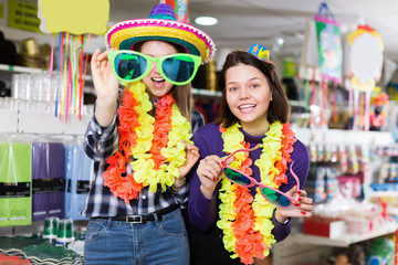 Happy female friends in comically outfits at decoration store