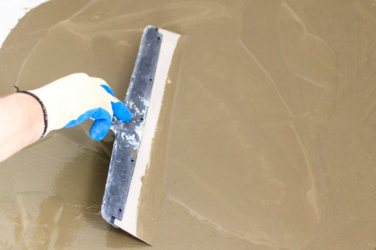 concrete floor. on it fly out to even out the horizon. close-up. worker with a spatula to drive the liquid across the floor