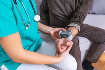 Nurse Visiting Senior man For Check Up. Young nurse measuring blood pressure of elderly man at home. Happy senior man having her blood pressure measured in a nursing home by her caregiver