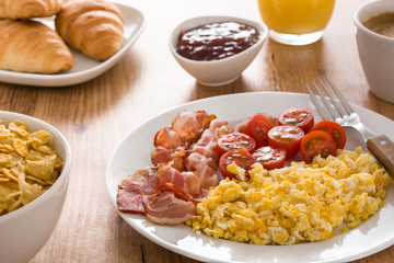 Breakfast with scrambled eggs, bacon, tomatoes,coffee,orange juice ,croissant and corn flakes on wooden table