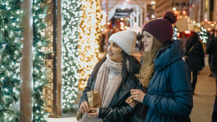 Two girls in New York look at Christmas decorated shop windows
