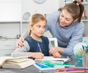 Woman helping her daughter with hometask