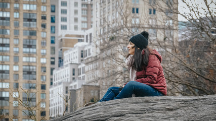 Young woman relaxes on a rock at Central Park New York