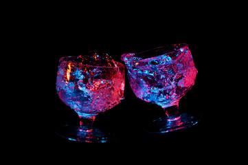 Glowing liquid splashing from fancy glasses