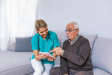Carer and senior man with tablet sitting on the sofa.