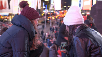 Two girls in New York enjoy the amazing view over Times Square by night
