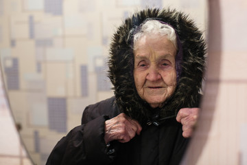 Old woman reflection in the mirror wearing winter outerwear.
