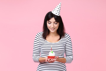 Young woman with birthday cupcake on pink background