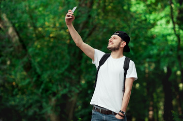 Smiling male taking a selfie against green trees. Man traveler in summer clothing standing outdoors taking selfie with her mobile phone