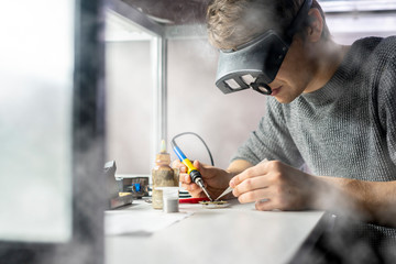 young scientist soldering microcircuit. science b