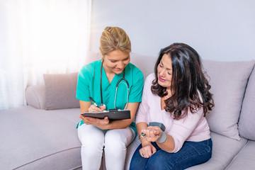 Nurse in home visit measuring blood pressure of old woman
