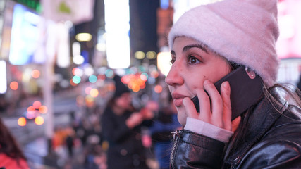Young woman takes a phone call on Times Square by night