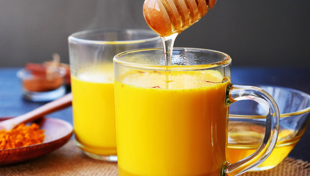 Sweetening saffron turmeric golden milk with honey. Honey is dripping from a wooden dipper in steaming  turmeric golden milk