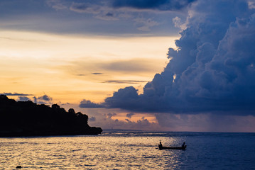 fishermen at sunset are seated on a boat in the ocean