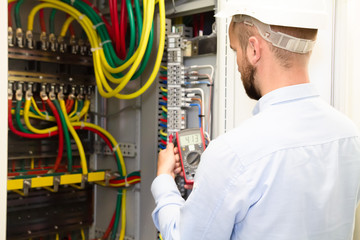 Electrician engineer working in electric fuse box uses tester.
