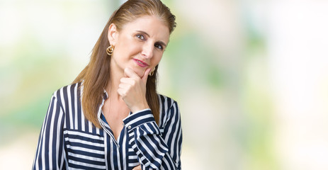 Middle age mature business woman over isolated background looking confident at the camera with smile with crossed arms and hand raised on chin. Thinking positive.
