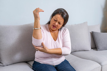 Senior woman suffering from pain in hand at home. Old age, health problem and people concept. Woman suffering from elbow pain. Elbow Pain In An Elderly Person
