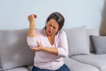 Elbow Pain In An Elderly Person. People, health care and problem concept - unhappy woman suffering. Senior woman suffering from pain in hand at home. Mature woman suffering from elbow pain at home