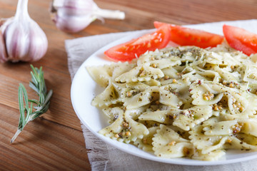 Farfalle pasta with pesto sauce, tomatoes and cheese on a linen tablecloth on a brown  wooden background.