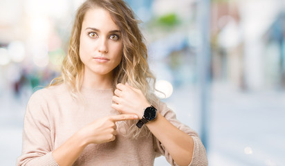 Beautiful young blonde woman wearing sweatershirt over isolated background In hurry pointing to watch time, impatience, upset and angry for deadline delay