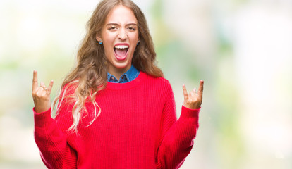 Beautiful young blonde woman wearing winter sweater over isolated background shouting with crazy expression doing rock symbol with hands up. Music star. Heavy concept.