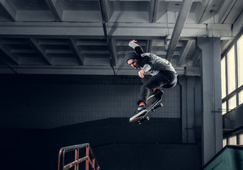 Skateboarder jumping high on mini ramp at skate park indoor.