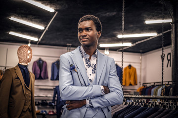 A handsome well-dressed African-American man posing with crossed arms in a classic menswear store.
