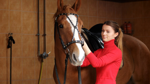 Beautiful girl with her horse in stable. Young woman adjusting her horse bridle before a ride. People and animals concept. Equine business.