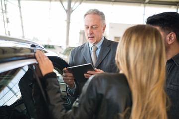 Young family talking to the salesman and choosing their new car in a showroom