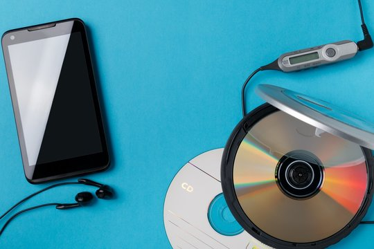 personal cd player with remote control and modern smartphone on blue background