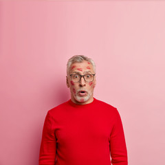 Vertical shot of astonished European male pensioner wears glasses, red jumper, has trace of kiss on cheek, isolated over rosy background with blank space for your promotional content or advert