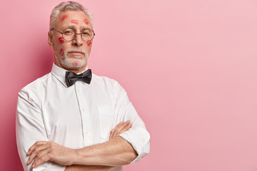 Self assured serious elderly man keeps hands crossed, looks with proud expression, has lipstick kiss, dressed in elegant formal clothes, poses over pink background with copy space for your text