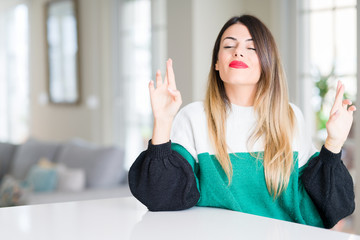 Young beautiful woman wearing winter sweater at home smiling crossing fingers with hope and eyes closed. Luck and superstitious concept.