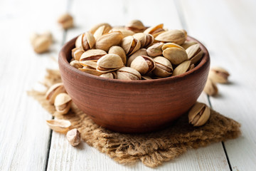 Salted pistachio nuts in ceramic bowl on white wooden background. Selective focus.