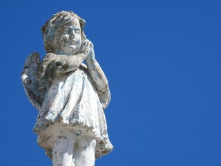 Scene in a cemetery: close-up of an old stone statue of a little angel with his hands clasped, praying. The statue is damaged by the passage of time. Clean and blue sky on a sunny day.
