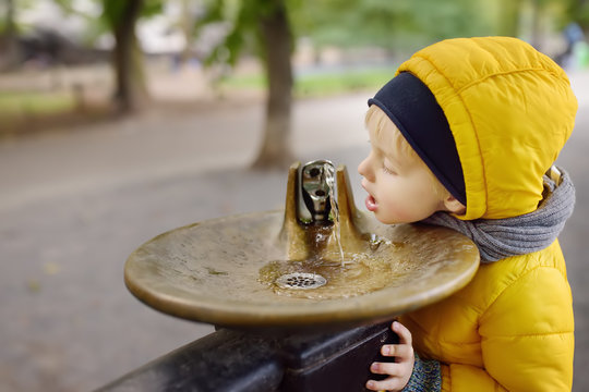Little boy drinking water from city fountain during walking in Central Park, Manhattan, New York, USA.