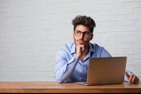 Young business man sitting and working on a laptop thinking and looking up, confused about an idea, would be trying to find a solution