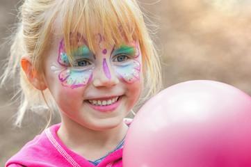 glückliches geschminktes Mädchen beim Kinderkarneval auf einem Freizeitpark mit einem Luftballon