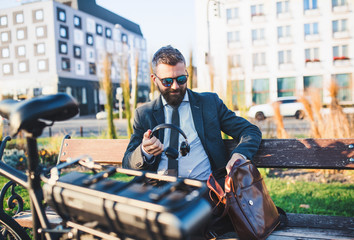 Businessman commuter with bicycle sitting on bench in city, holding headphones.