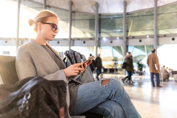 Casual blond young woman using her cell phone while waiting to board a plane at the departure gates at the airport terminal.