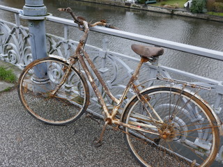 Old rusty lady's bicycle, parked at a bridge railing and then forgotten
